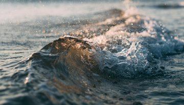 Sfeerbeeld bij het blog over de bevrijding via het woord 'moeten'. Wateroppervlak van de zee, close-up van een kleine golf. Zijaanzicht. De onstuimigheid van de beweging extra zichtbaar via losse spetters. In antracietblauw, ijsblauw en brons.