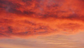Sfeerbeeld bij dialoogblog over gedachten aan zelfmoord. Een hemel bedekt met wolken, in de avondzon. Onderin regelmatig crème en lichtblauw. Midden en bovenaan onstuimig rood, oranje, paars.