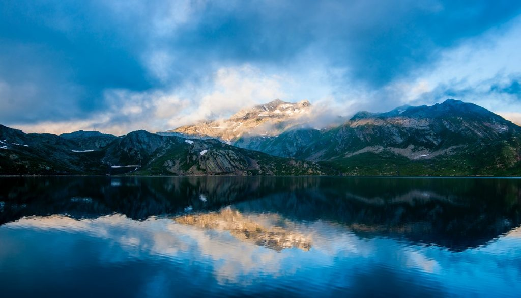 Sfeerbeeld bij een dialoogblog met een jongere met TOS, Een vulkaanlandschap, in ruste. In blauw, zwarte, groen, wit en geelbruin. Het landschap wordt weerspiegeld in het meer op de voorgrond. Omgeven door wolken.