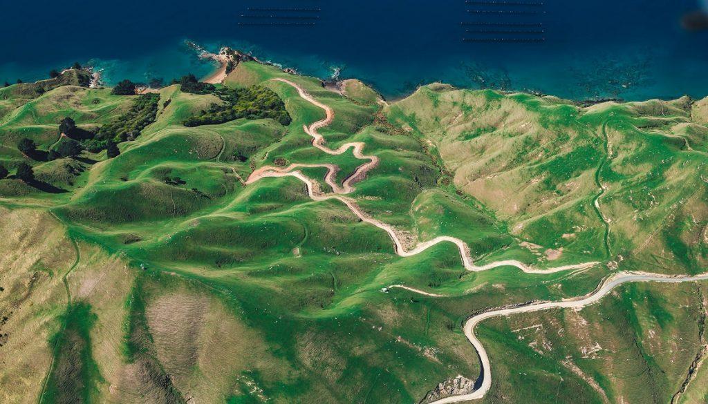 Sfeerbeeld bij dialoogblog over werkloosheid en stilstand. Bovenaanzicht van een berglandscha, in groen en zandkleur, met een lichte kronkelige weg, richting de zee. De zee in donkerblauw, bovenaan de foto.