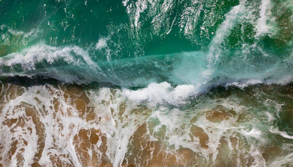 Sfeerbeeld bij dialoogblog over niet bij jezelf zijn. Bovenaanzicht van een golf die klotsend op het strand slaat. In zeegroen, wit en oranjebruin.