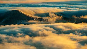 Sfeerbeeld bij blog De leeuw, het hertje en de danser. Een foto van een wolkendek dat over bergen heen golft. In zeeblauw, donkerbruin, wit en goudgeel.