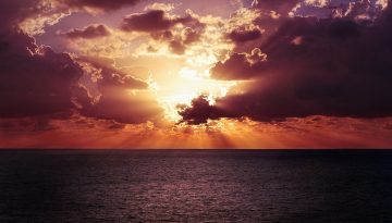 Sfeerbeeld bij blog 5 over anonieme cliënt Michal. Een vlakke zee, met aan de horizon een schitterende ondergaande zon, tussen de wolken door, in paars, geel en oranje.
