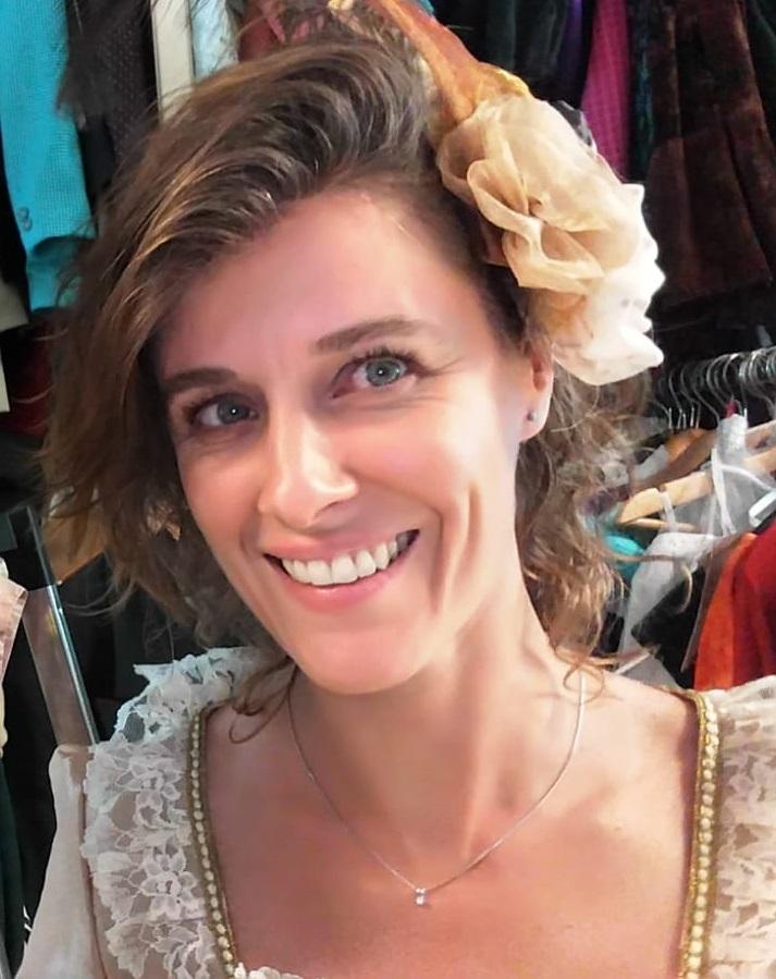 Foto van Ilona Kuis. Ze kijkt lachend schuin naar rechts, en draagt een bloemenspeld in haar haar.