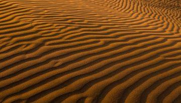 Sfeerbeeld bij blog 'Waar gaat dit gesprek heen?'. Beeld van roestbruin woestijnzand in regelmatige lijnen verdeeld door de wind.