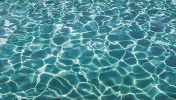 Sfeerbeeld bij blog van cliënt Jim deel 1. Een beeldvullende weergave van een zeegroene waterspiegel, door het licht en de beweging onderverdeeld in gevarieerde compartimenten met een witte rand.