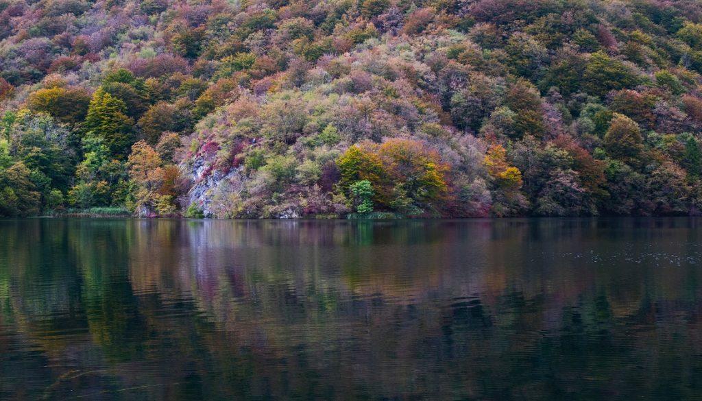 Sfeerbeeld bij blog 4 van cliënt Jim. Vooraanzicht van berg, begroeid met bomen in herfstkleuren, op de voorgrond de weerspiegeling ervan in een stil meer.